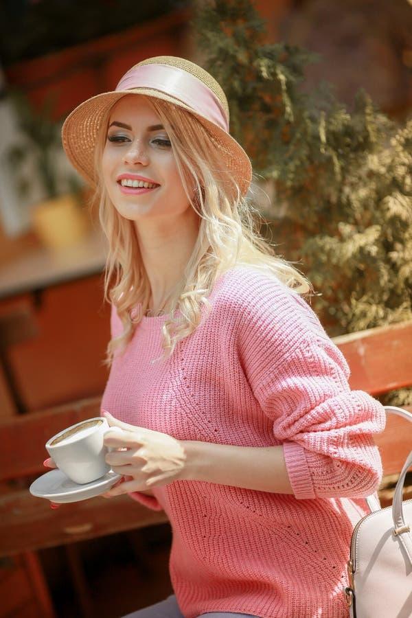 浪漫心情的可爱的妇女微笑在幸福的坐对穿桃红色夹克的桌 库存照片