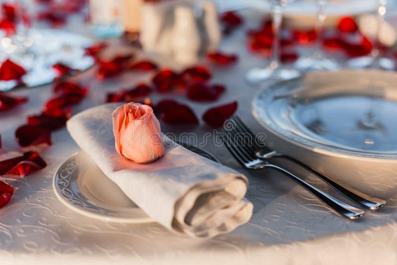 浪漫情人节晚餐设定与玫瑰花瓣 免版税库存照片