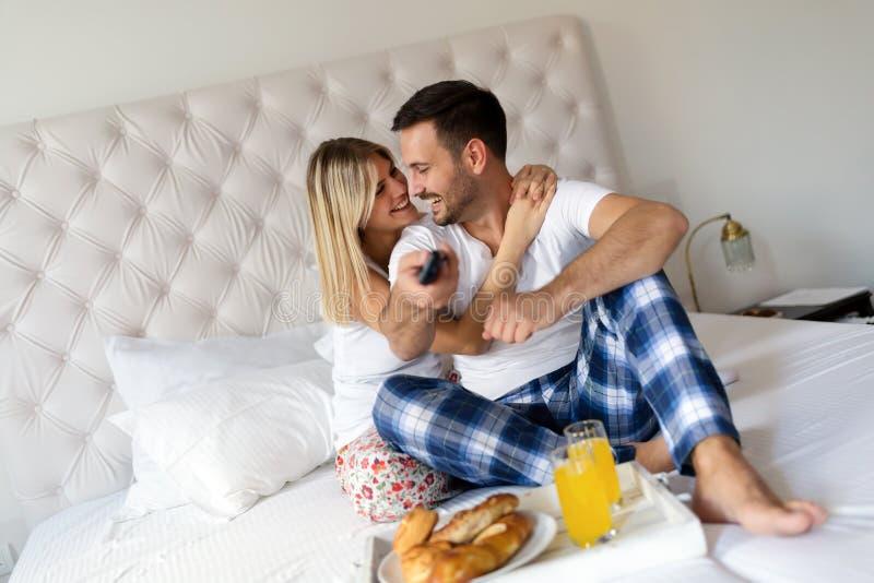 浪漫愉快的夫妇吃早餐在床 免版税图库摄影