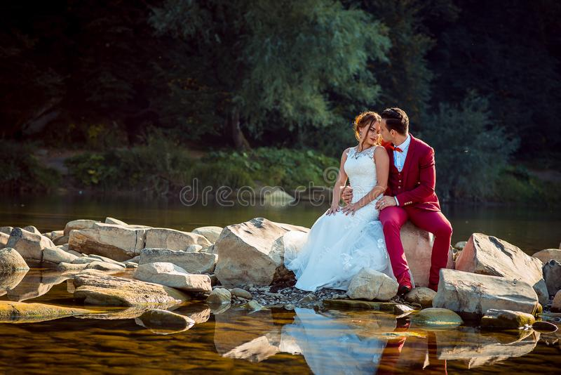 浪漫拥抱美好的爱恋的新婚佳偶的夫妇的婚礼室外画象,当坐石头在附近时 免版税库存照片