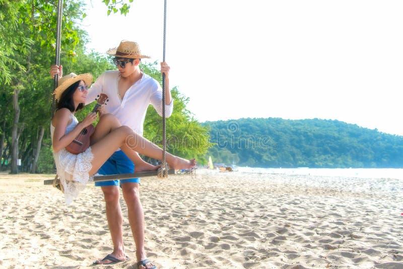 浪漫播放在吊床的生活方式亚裔夫妇恋人尤克里里琴 在海滩附近放松和蜜月在豪华旅游胜地 库存照片