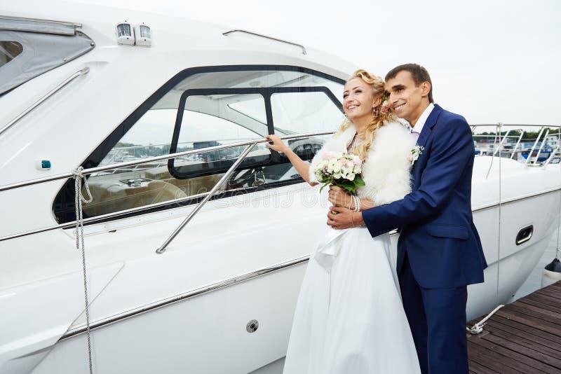 浪漫新娘和新郎在码头有游艇的 库存图片