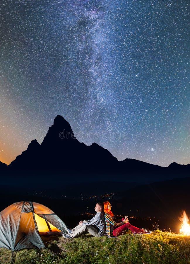 浪漫旅游夫妇-坐由营火的女孩和人在光亮的帐篷附近在美丽的满天星斗的天空和银河下 免版税图库摄影