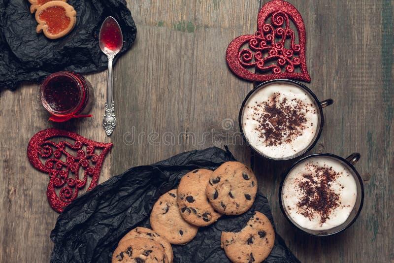 浪漫早餐两杯咖啡、热奶咖啡用巧克力曲奇饼和饼干在红色心脏附近在木桌背景 库存图片