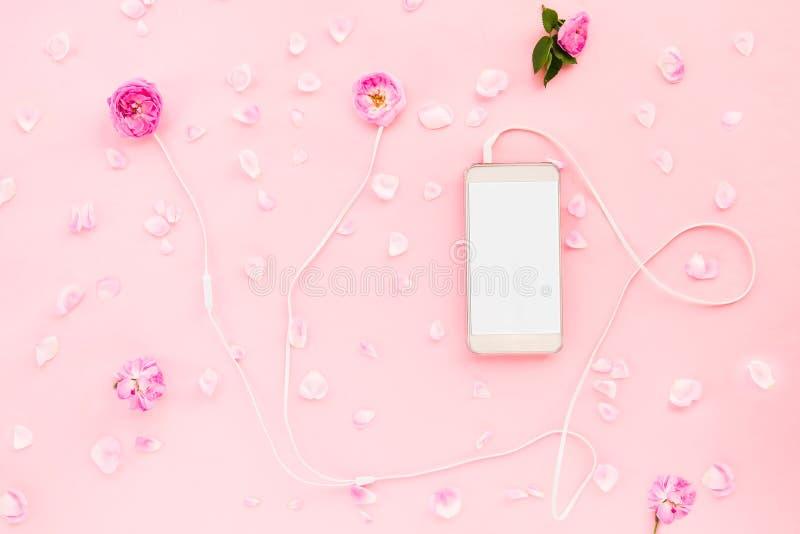 浪漫时尚布局-有桃红色玫瑰的顶视图白色耳机开花,智能手机和玫瑰花瓣在桃红色背景 rel 库存照片