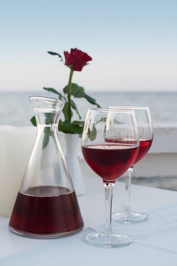 浪漫晚上饮用的红酒在海的餐馆 免版税库存图片