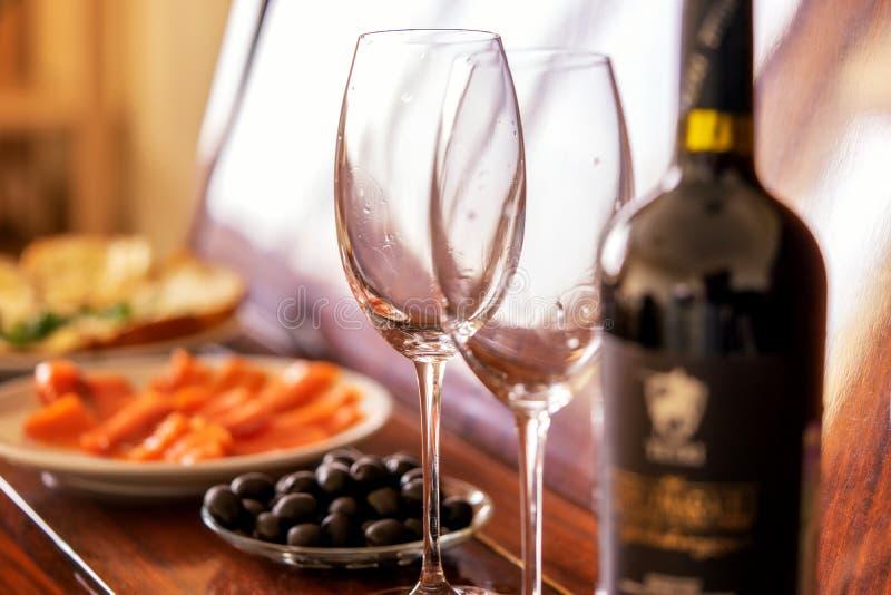 浪漫晚餐和红酒 盘在钢琴:鱼,橄榄,玻璃 库存照片
