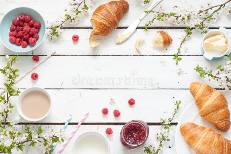 浪漫法国或农村早餐用新月形面包、果酱和莓在白色 免版税库存图片