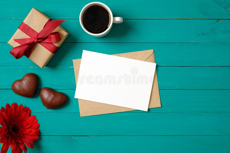 浪漫爱概念 与白纸卡片,礼物盒,信封,心形的巧克力,花,杯子的平的被放置的构成  免版税图库摄影