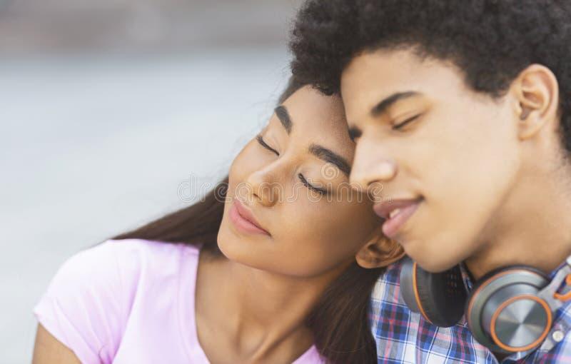 浪漫片刻 坐与他们的眼睛的梦想的青少年的夫妇关闭了 免版税库存图片