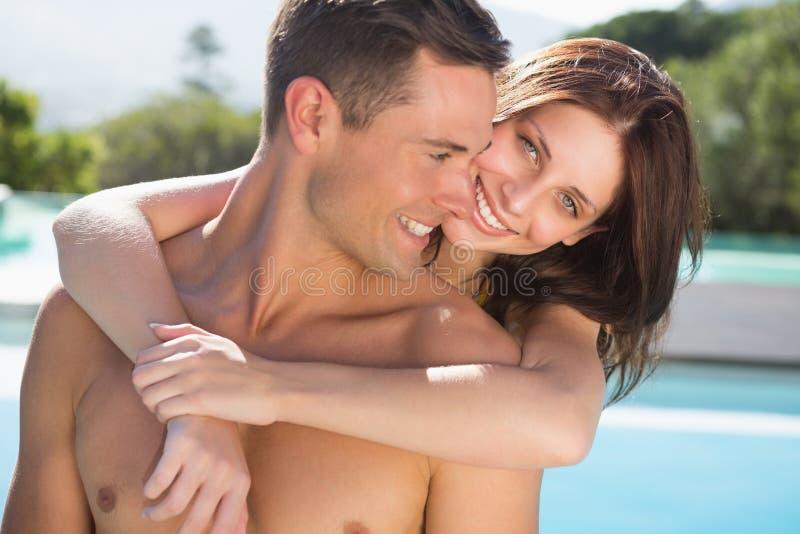 浪漫由游泳池的妇女拥抱的人 图库摄影