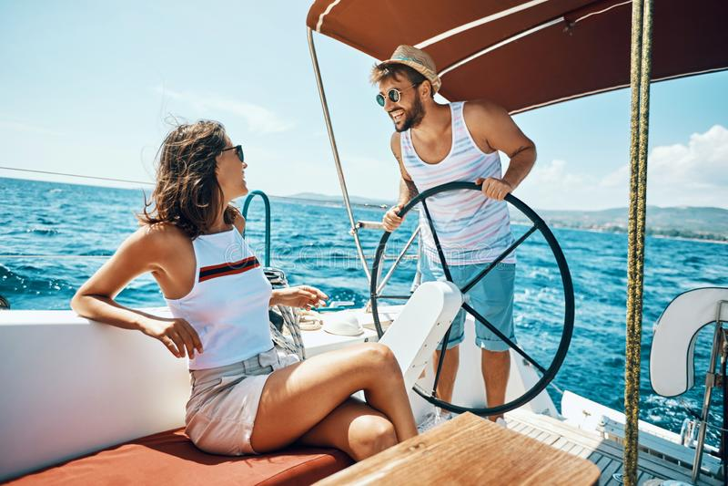 浪漫男人和妇女游艇的在度假享受明亮的好日子 免版税库存图片