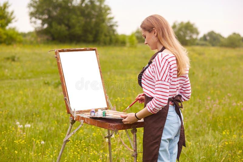 浪漫白肤金发的白色偶然衬衣的长发卷曲女性艺术家有红色条纹、蓝色站立裤子和棕色的围裙的近 免版税库存图片