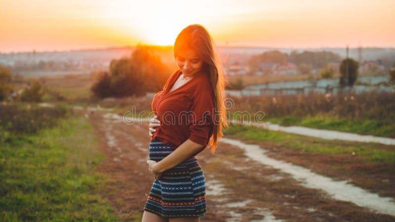 浪漫的秀丽是享受自然的怀孕的女孩户外拿着她的腹部美好的秋天模型本质上在日落光芒的  库存图片