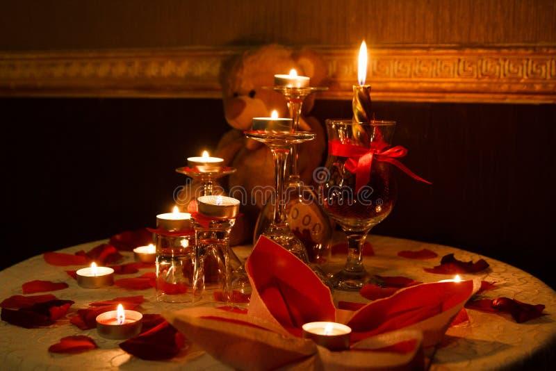 浪漫装饰桌设置了与蜡烛、玻璃、玫瑰和玩具熊,黑暗的温暖的口气, 库存照片