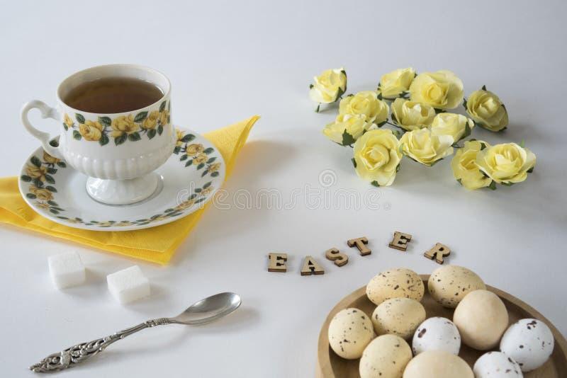 浪漫黄色复活节场面用茶、复活节彩蛋、匙子和玫瑰 免版税图库摄影