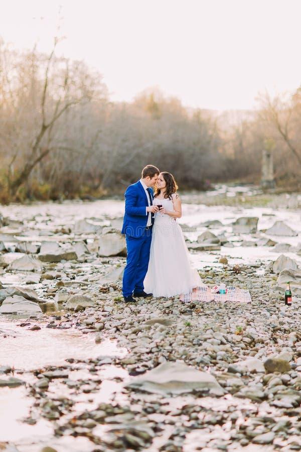 浪漫年轻新娘在岩石小卵石河岸的夫妇饮用的酒有Forest Hills和小河的 免版税库存照片