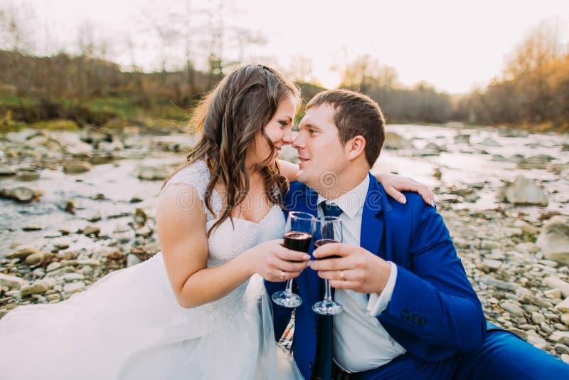 浪漫年轻新娘对在小卵石河岸的饮用的作为背景的酒有小山的和小河 免版税库存照片