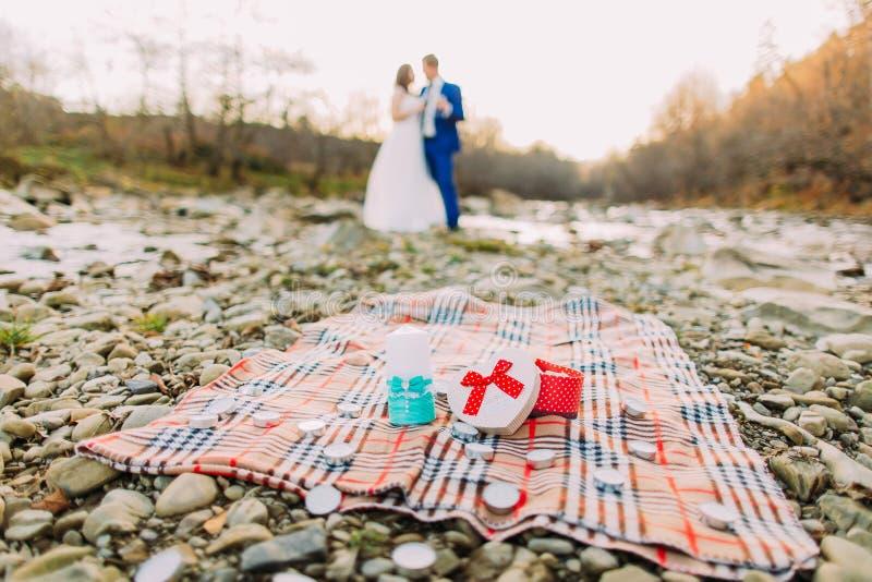 浪漫年轻新娘对在小卵石河岸的饮用的作为背景的酒有小山的和小河 免版税图库摄影