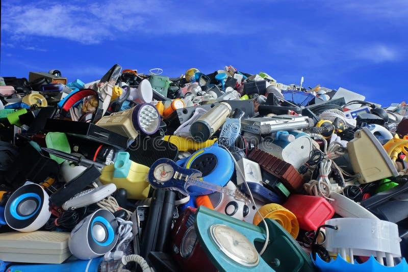 浪费分部打破的堆半新电子和家庭用品或损坏与蓝天并且覆盖背景 免版税库存照片