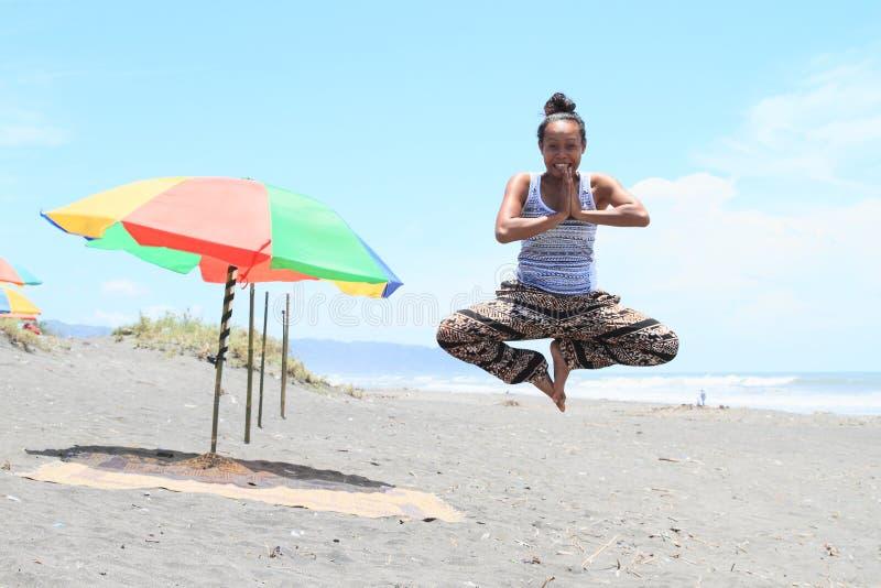 浮动在海滩的瑜伽姿势的女孩 免版税图库摄影