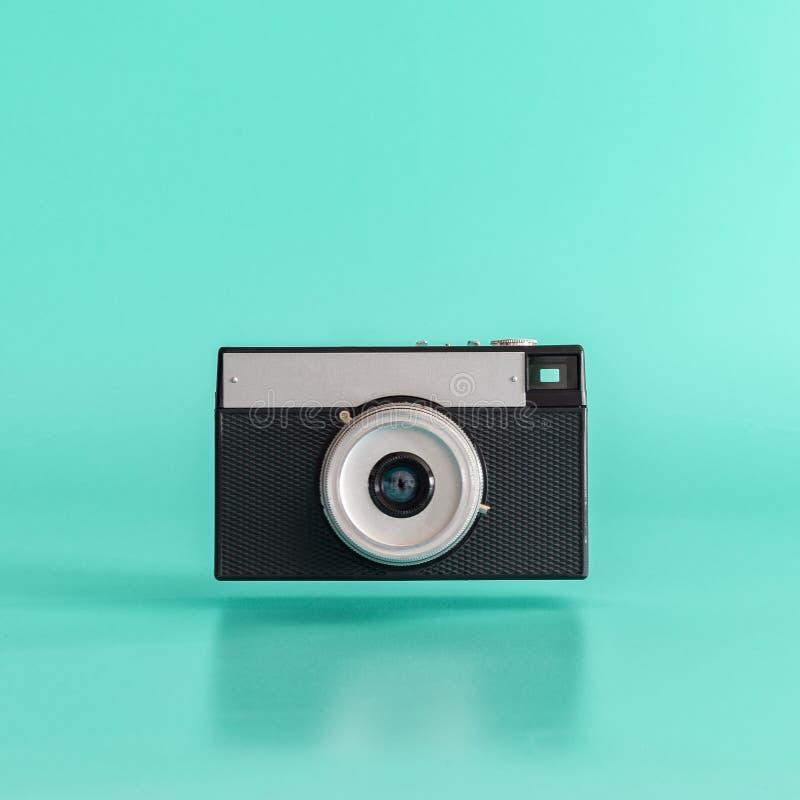 浮动在蓝色背景的老黑胶卷相机 最小的概念 库存照片