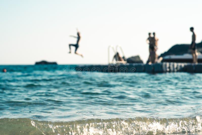 浮动平台在海,当少年获得乐趣,在焦点外面 库存照片