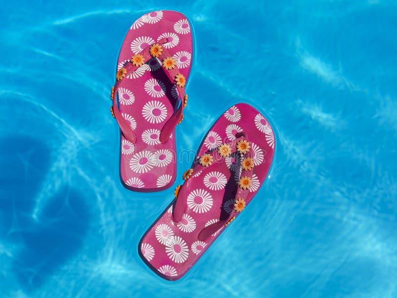 浮动池游泳的五颜六色的塑胶人字平底拖鞋 免版税图库摄影