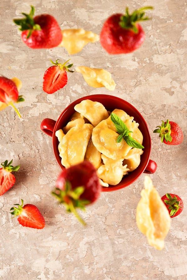 浮动的食物 Pierogi 饺子用用草莓飞行 r 库存图片