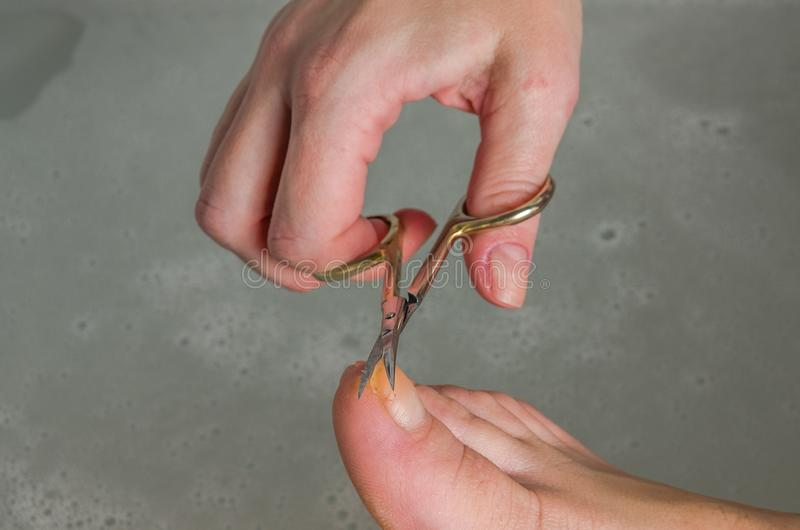 浴的一名妇女剪她的钉子,做在她的腿的修指甲 免版税图库摄影