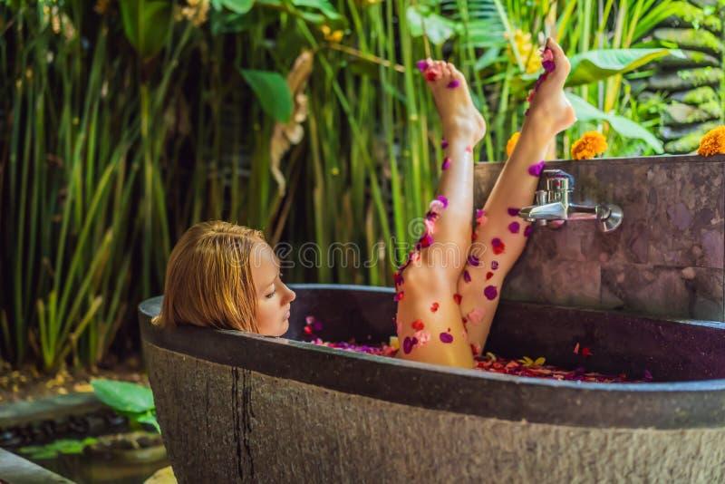 浴的可爱的年轻女人与热带花和芳香油的瓣 皮肤回复的温泉治疗 图库摄影