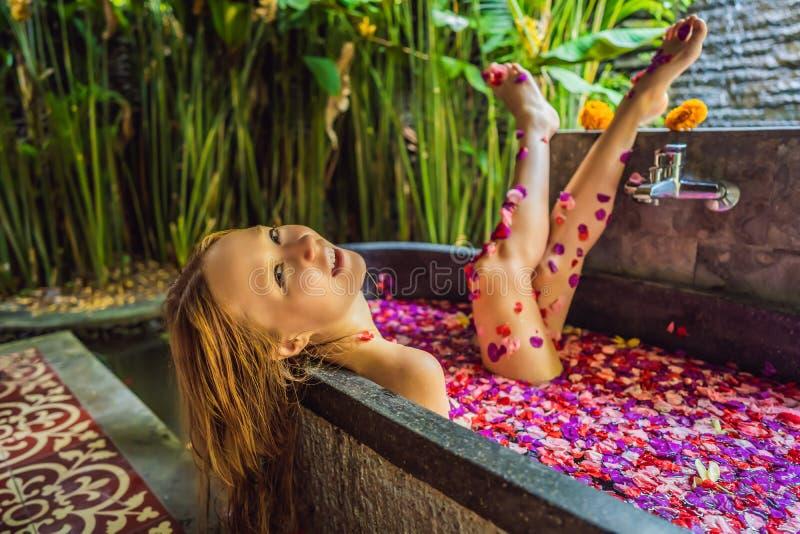 浴的可爱的年轻女人与热带花和芳香油的瓣 皮肤回复的温泉治疗 免版税库存照片