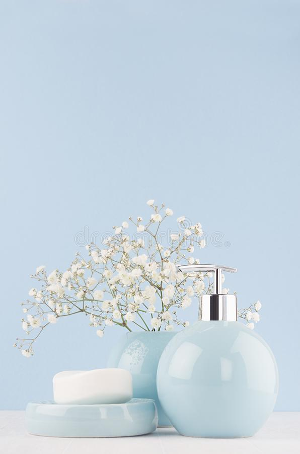 浴的轻的淡色蓝色辅助部件和皮肤和身体关心产品-肥皂,肥皂分配器,在白色木桌上的毛巾 免版税图库摄影