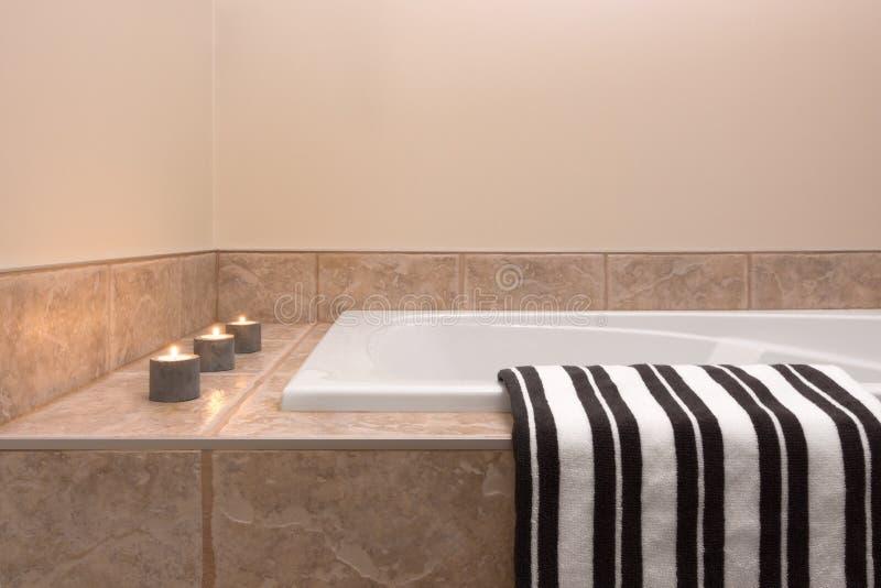 浴缸、镶边毛巾和蜡烛光 库存照片