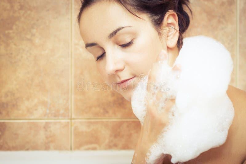 浴缸泡沫充分的妇女 免版税库存照片