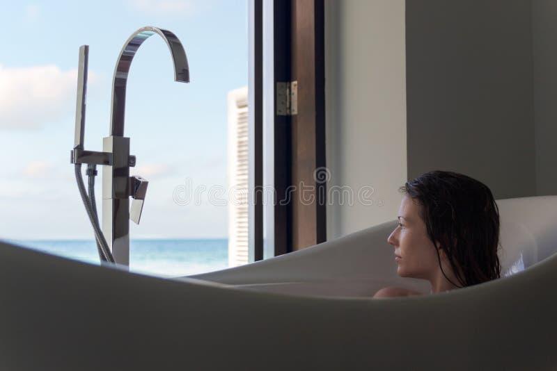 浴缸的年轻女人敬佩从窗口的看法 热带假日目的地 库存照片