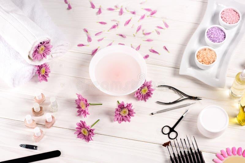 浴顶视图钉子的在与花,瓣,毛巾,指甲油,指甲锉,表皮推者,指甲夹的桌上, 免版税库存照片