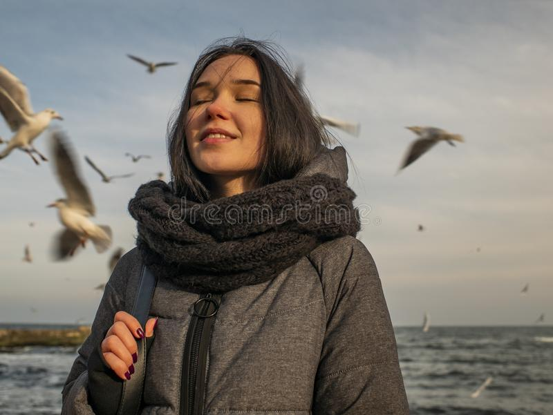 海、天空和鸥的背景的画象年轻可爱的女孩 免版税库存图片