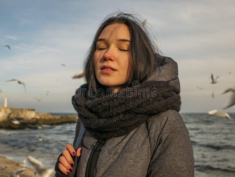 海、天空和鸥的背景的画象年轻可爱的女孩 免版税图库摄影