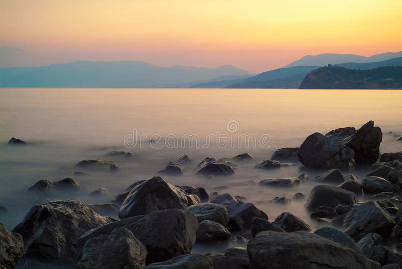 海、岩石和山在日落以后在夏天 免版税库存图片