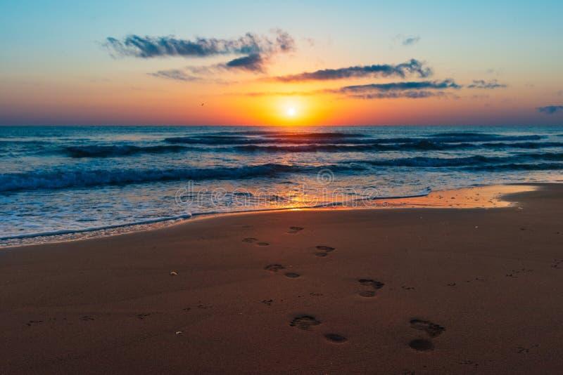 海上的惊人的五颜六色的日出,在沙子的脚印 免版税库存照片