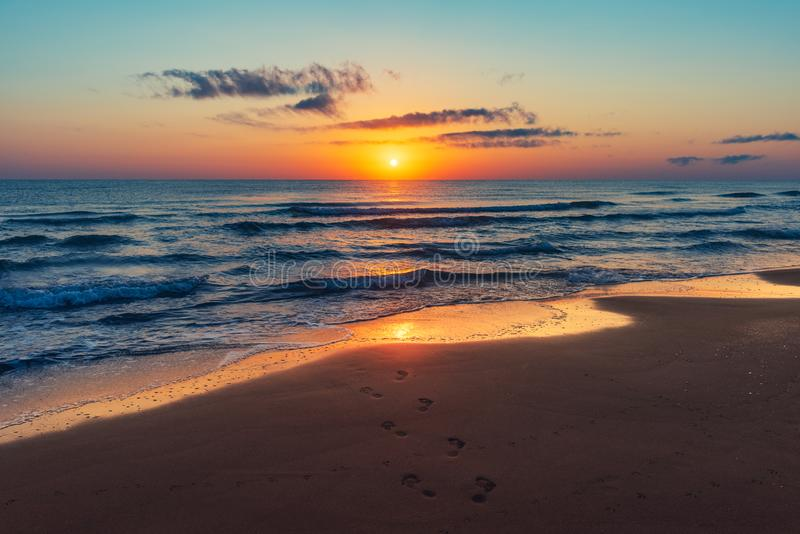 海上的惊人的五颜六色的日出,在沙子的脚印 免版税库存图片