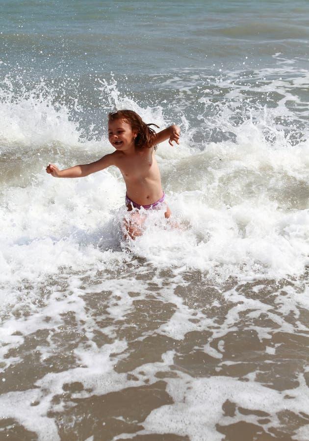 海上的愉快的孩子有波浪的 免版税库存图片