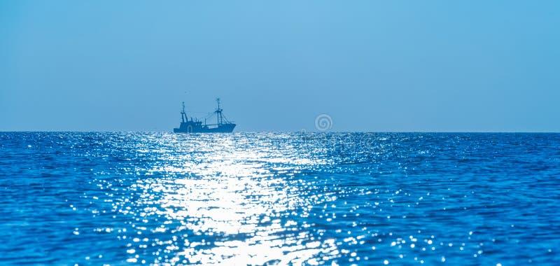 海上的拖网渔船渔日落的 库存图片