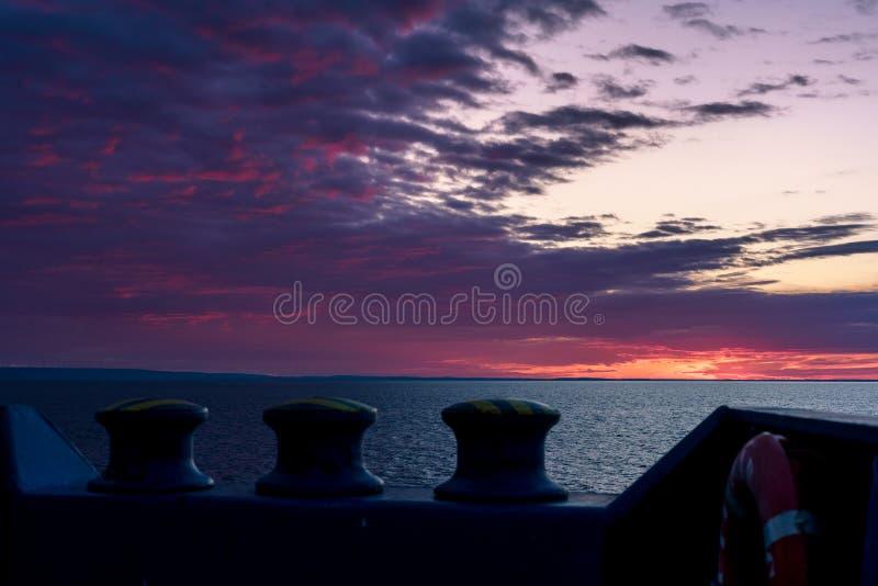 海上的晚上 落日美妙地上色在温暖的颜色的天空 ?? r 库存图片