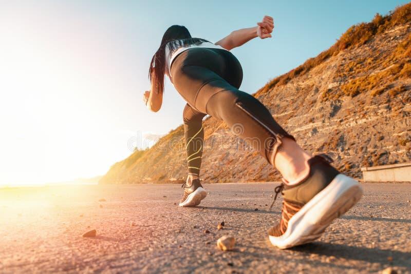 海上运动与慢跑 女人随时准备跑 背景中,山和太阳 底视图 图库摄影