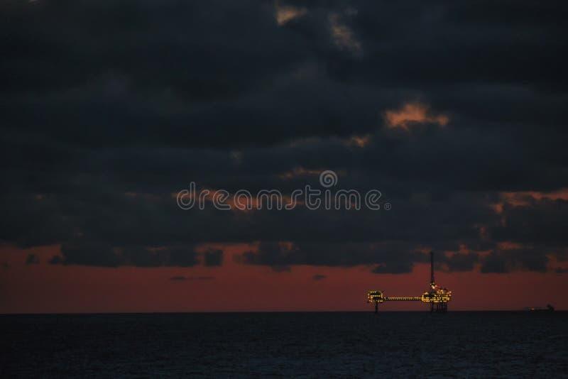 海上钻探钻机建设中 石油工业结构 石油平台在晚上 免版税库存照片