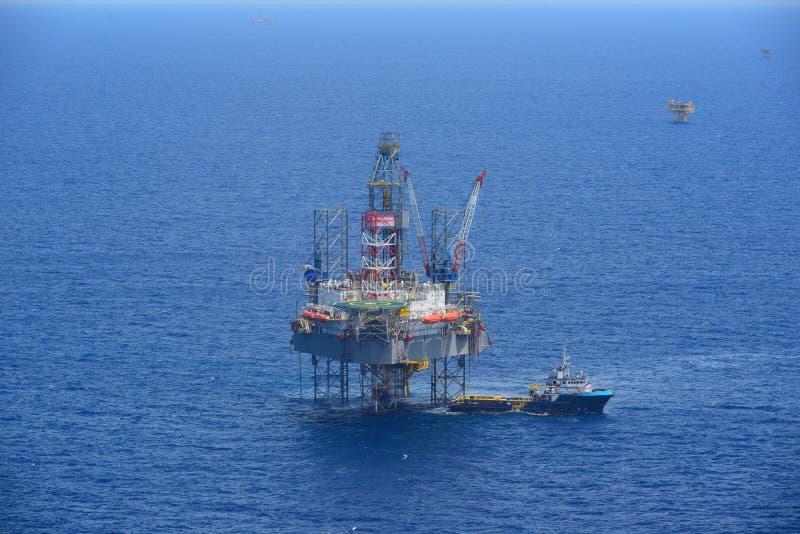 海上钻井抽油装置和供应小船侧视图 库存照片