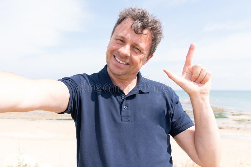 海假期嘲笑海滩的愉快的人采取selfie电话 库存照片