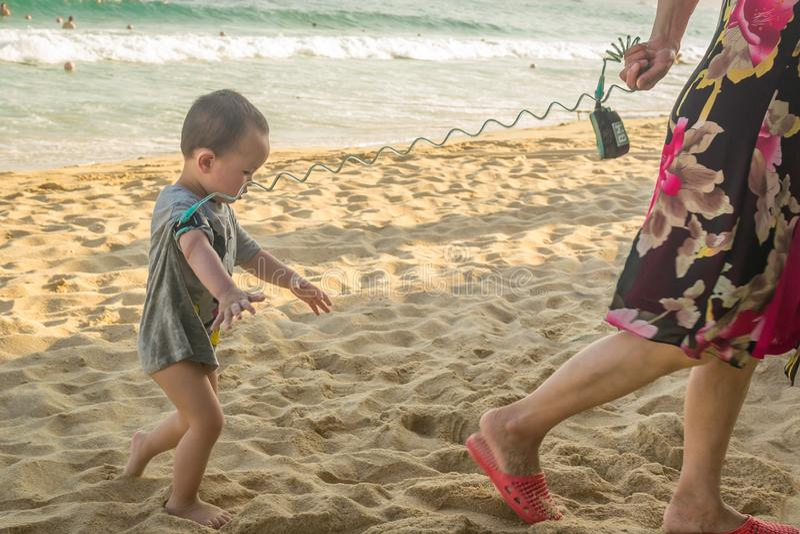 海南,中国- 2019年5月15日:妇女带领在海滩的一条皮带栓的一个小孩子 图库摄影